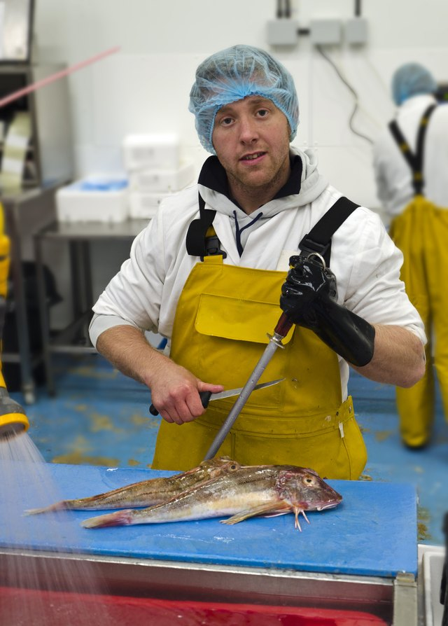 A worker in a fish market wears a hair net, gloves, and apron.