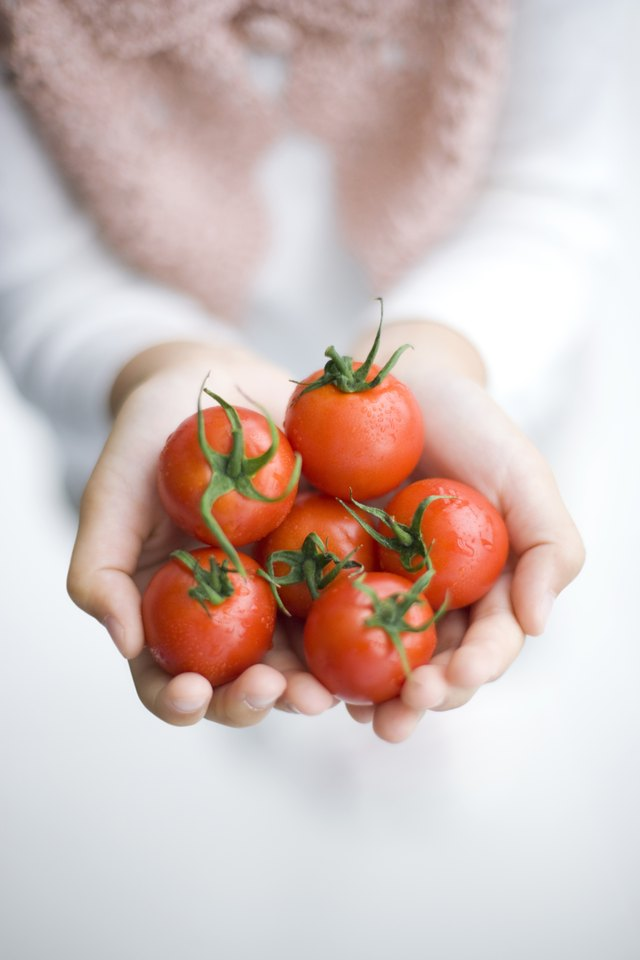 A girl is holding cherry tomatoes.