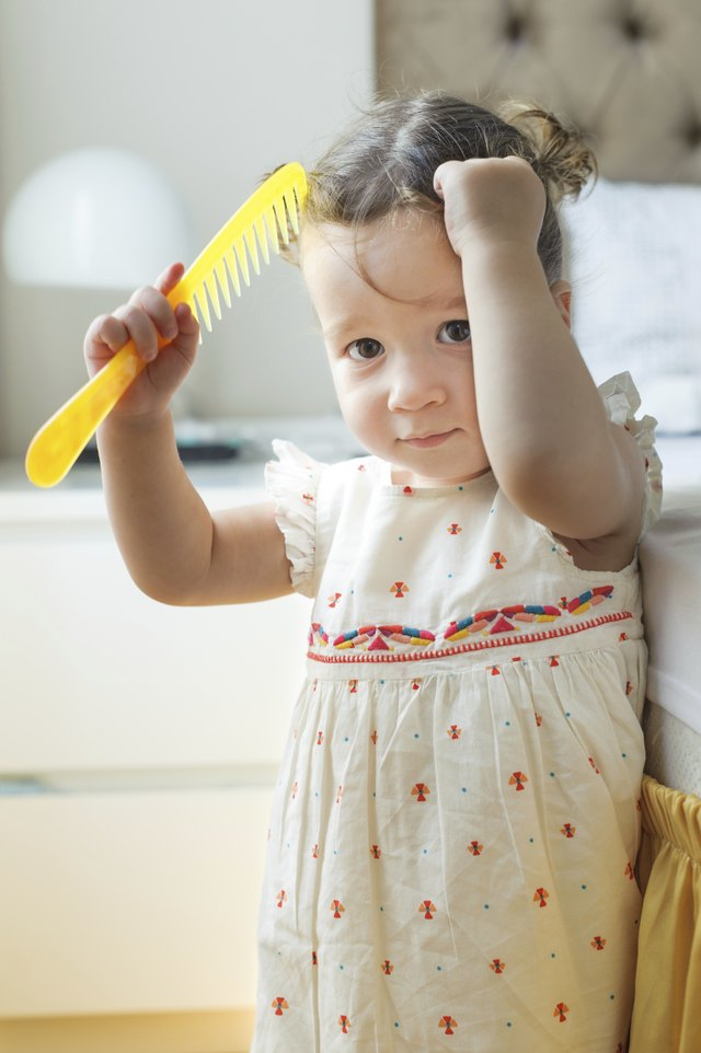 A toddler combs her hair.