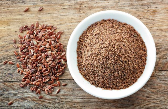 A bowl of crushed flaxseeds next to whole flaxseeds
