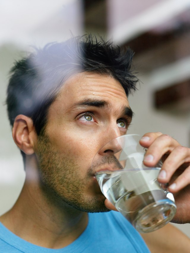 Young man drinks a glass of water