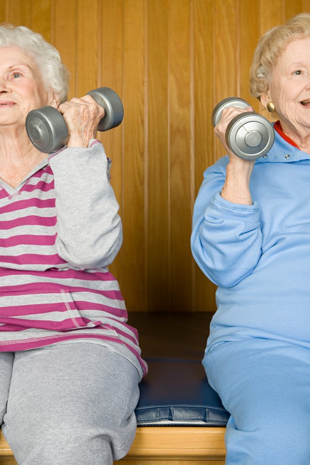 Two mature woman lift light weights