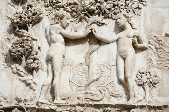 A close-up of a relief sculpture of Adam and Eve holding the serpent in the garden.
