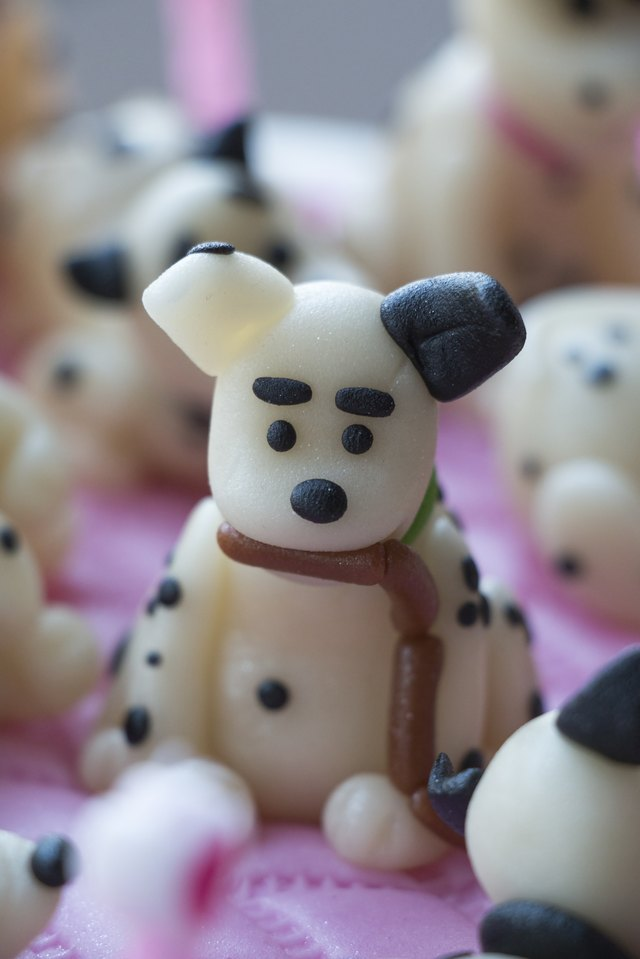A marzipan shaped dalmation puppy with sausage in his mouth