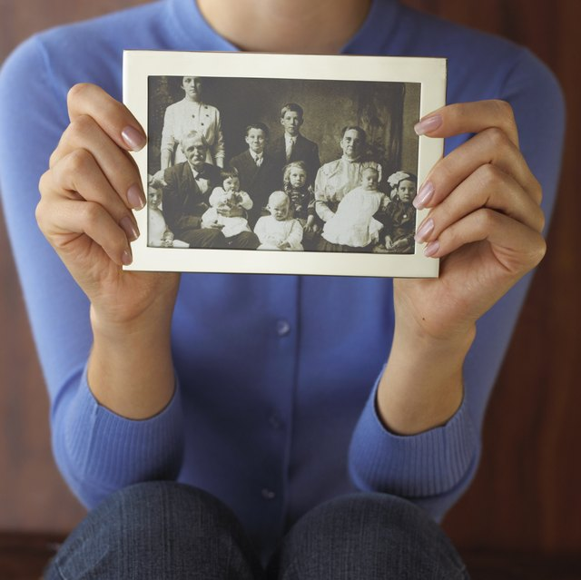 A woman holds up a photograph.