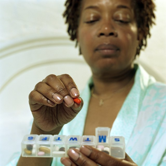 Close-up of woman taking iron supplement out of vitamin pack.