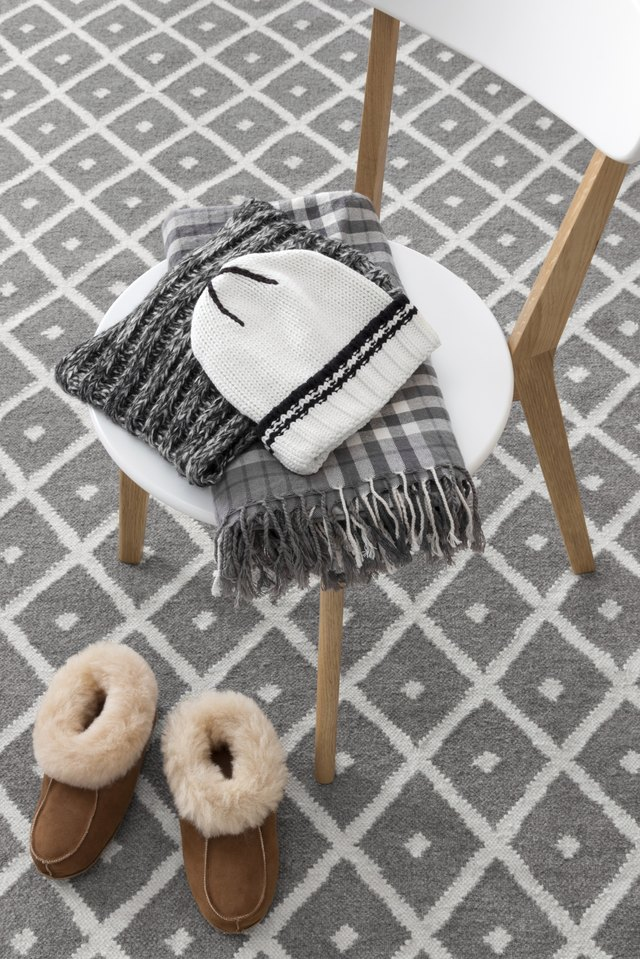 Close-up of a wool hat and scarf laying on a chair.