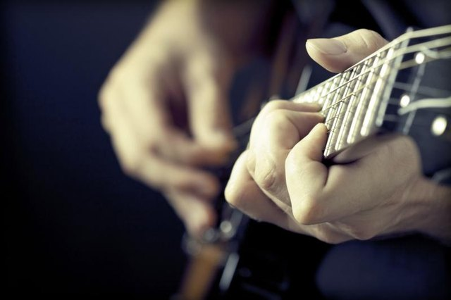 Hands playing a guitar.