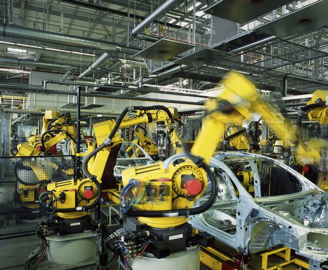 Yellow robots manufacturing cars in a factory