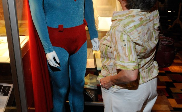 A woman looks at a Superman costume on a mannequin.