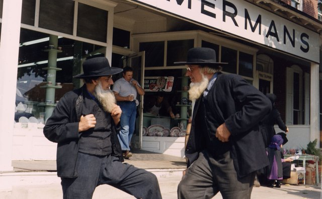 Two Amish men stand in front of a store in town.