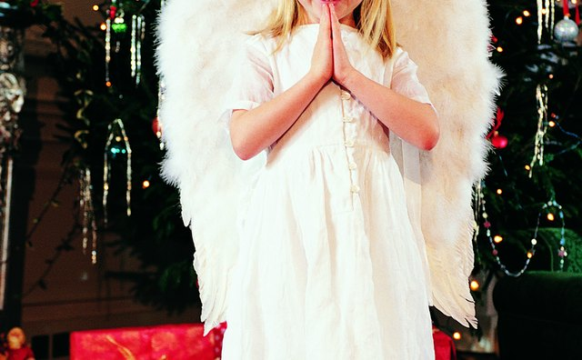 Little girl dressed as an angel with wings.