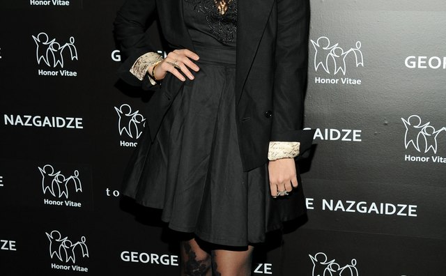 Vanessa Hudgens wears black lace tights with a black dress for a chic monochromatic look.