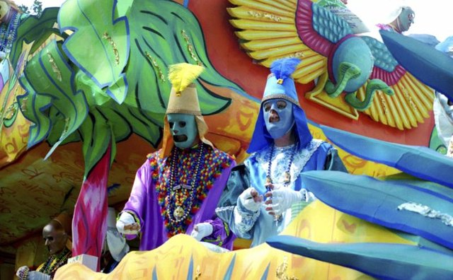 People dressed in costume on a Mardi Gras themed float.