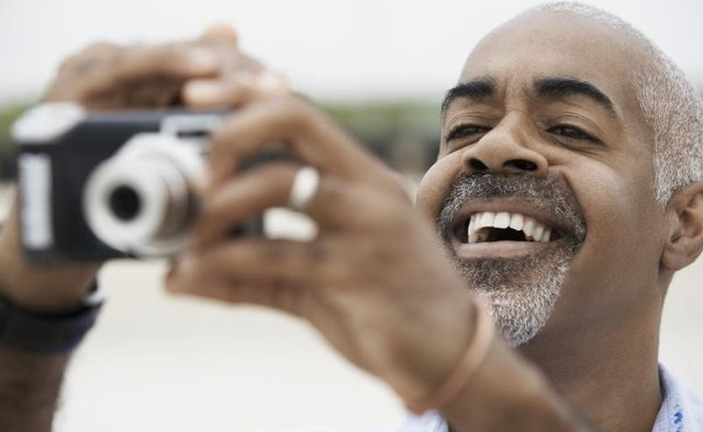 Man using a digital point and shoot camera.
