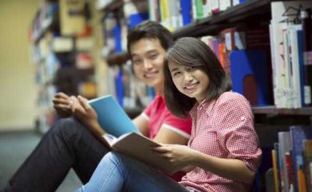 Young couple smiling at camera in library