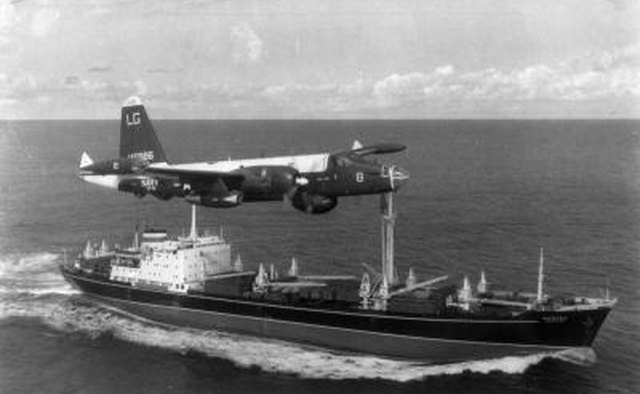 A P2V Neptune U.S. patrol plane flies over a Soviet freighter during the Cuban missile crisis in this 1962 photograph.