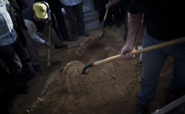 People shovel dirt at funeral