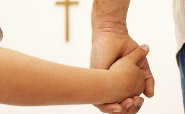 Parent and child holding hands, cross in background.
