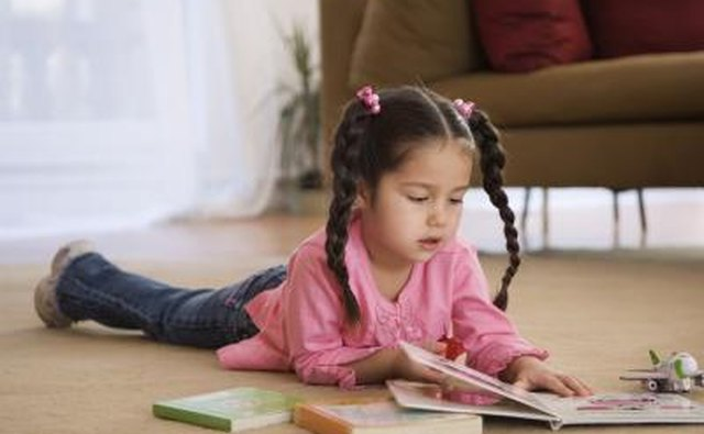 Young child reading book on floor