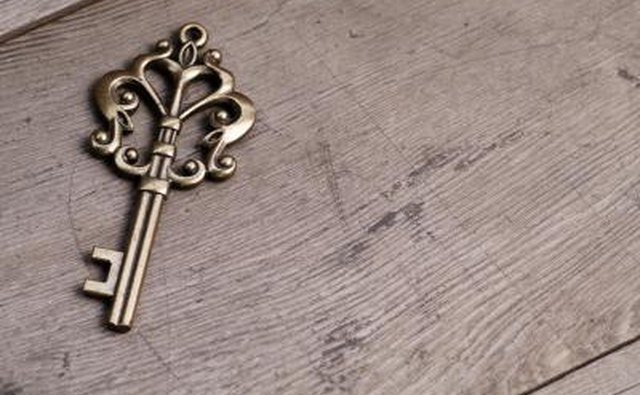 A gold skeleton key in the shape of a heart.