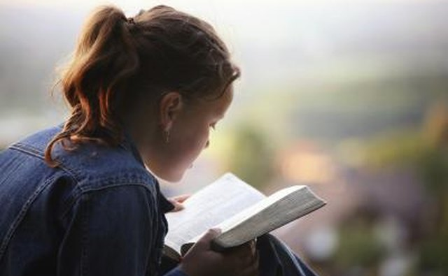 Reading a Bible outdoors.