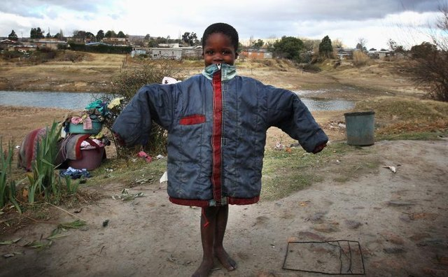 A young orphan holding up a donated coat.