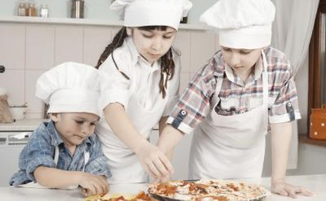 Young children making a pizza