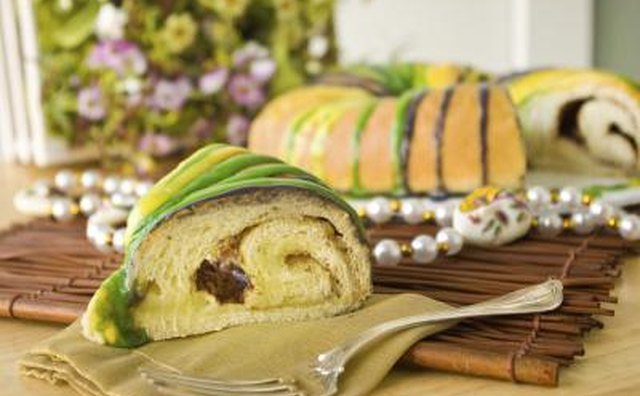 A slice of New Orleans king cake on a wooden mat with decorative beads.