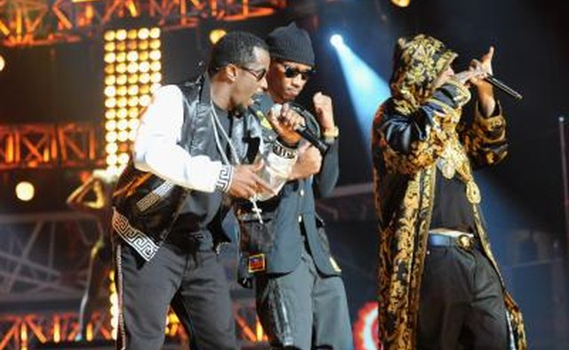 Three hip hop artists perform on stage.