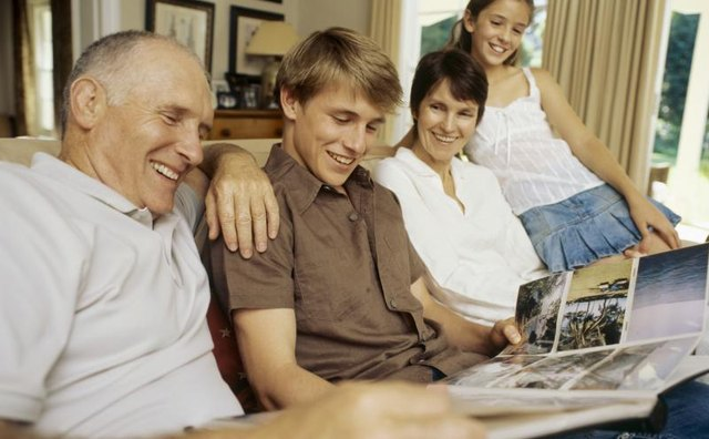 A man looking at a photo album with his family on the sofa.