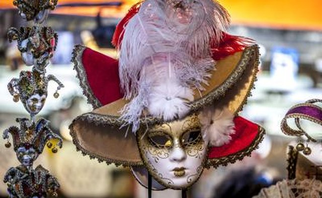 A Mardi Gras mask and feathered hat on a mannequin in a costume shop.
