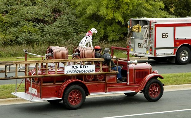 A Dalmatian sits on top of a fire engine.