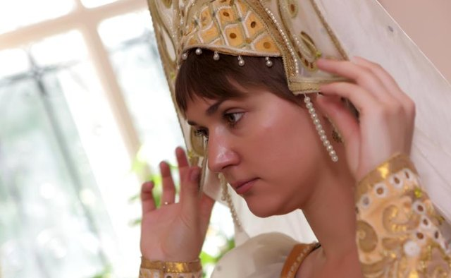 A woman adjusting a kokoshnik.