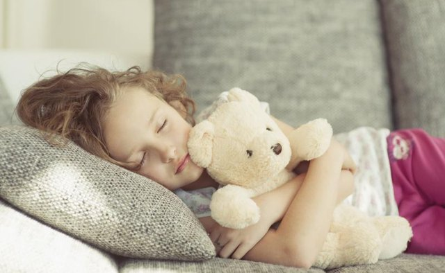 Girl sleeping with a stuffed teddy bear.