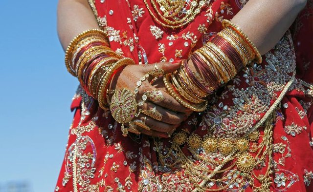 A woman displays bangles on her wrists.