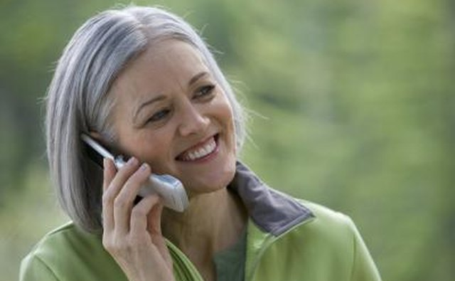 Mature woman talking on phone outdoors.