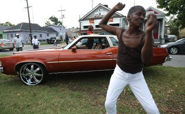 A woman dances to a car stereo on a lawn in New Orleans.