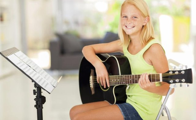 Girl holding guitar next to sheet music