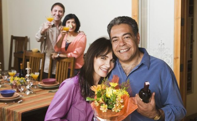 Older couple smiling at dinner party.
