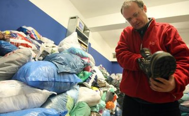 A volunteer checking the condition of a shoe in a homeless shelter.