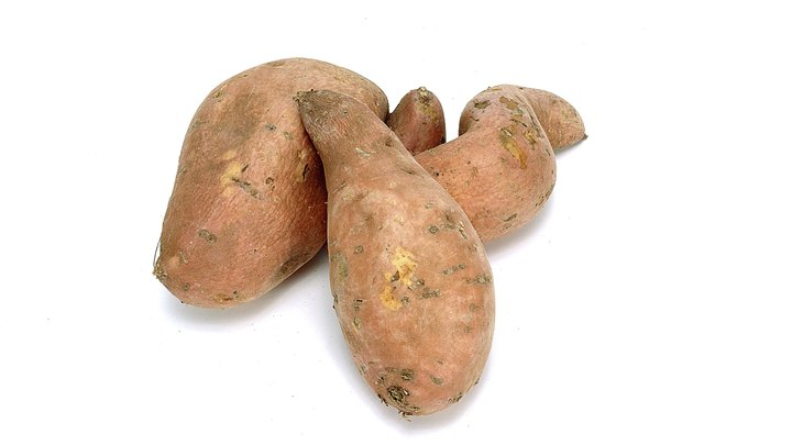 Sweet potatoes appear on many U.S. Thanksgiving and Christmas tables, but you can find them throughout the year. This root is high in antioxidants, vitamin A and has a lower glycemic index than white potatoes. Popular cooking methods for sweet potatoes include baking or boiling. You can bake sweet potatoes in the oven or microwave. Either baking method offers you some advantages.