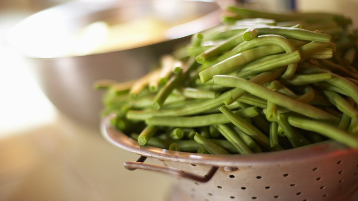 Green beans -- also called string beans -- have an edible pod and are either grown on bushes or attached to garden poles much like vines. Unlike many other legumes, green beans can be eaten raw without much concern for digestive problems. Raw green beans are rich sources of dietary fiber and a variety of other nutrients, which makes them a healthy choice.