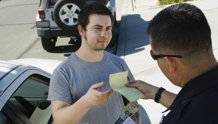 Police officer handing ticket to young driver