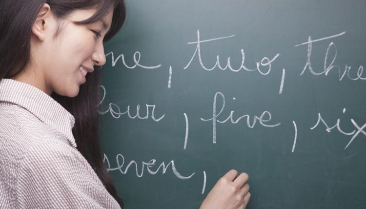 Language student writing numbers out on chalkboard