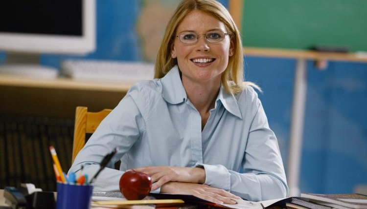 Smiling teacher sitting at desk with paperwork
