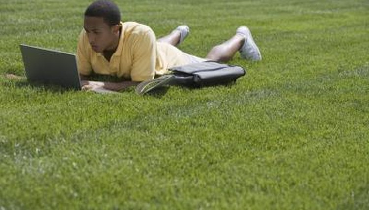 Student working on laptop on grass field.