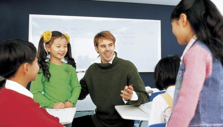 Teacher talking with young students in classroom