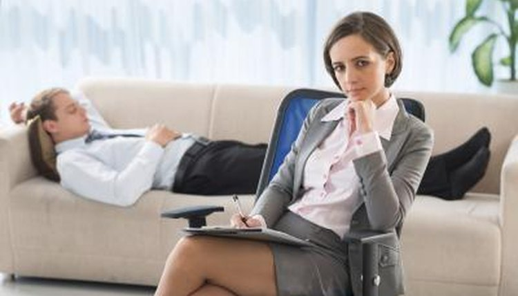 Counselor sitting on chair with client on couch in background