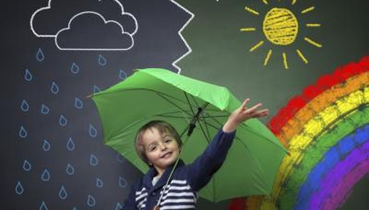 Kindergarten student with umbrella in front of rain and sun chalk drawing.
